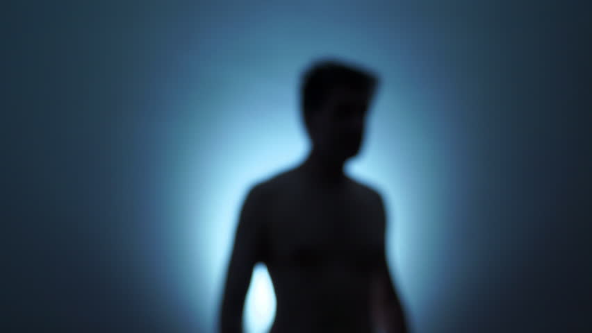 Unfocused backlit naked man moves his hand to say hello. Near-death experience. Alien image.