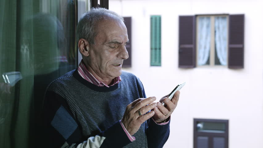 old man trying to watch some video on youtube with mobile phone