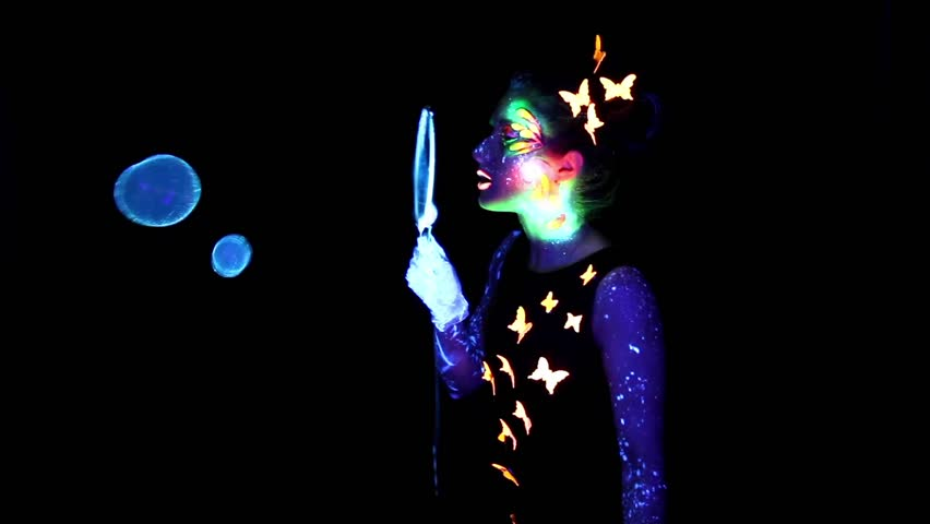 Video of woman with luminous make up playing with bubble in darkness - HD stock footage clip