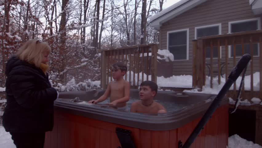 an older woman wearing a winter jacket disciples two young boys in a hot tub stock footage video. Black Bedroom Furniture Sets. Home Design Ideas
