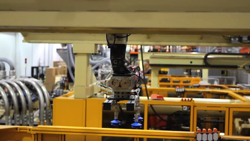 Multiple robotic arms move back and forth in this factory.  - HD stock video clip