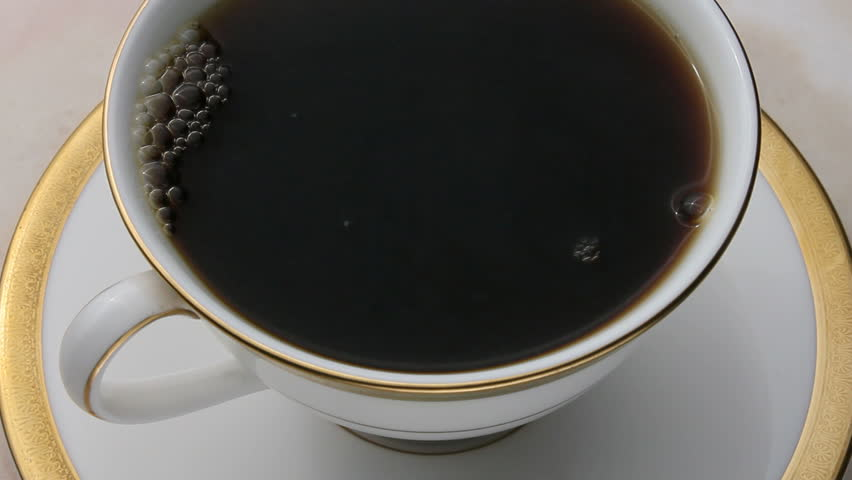 Coffee being poured into an elegant cup - HD stock video clip
