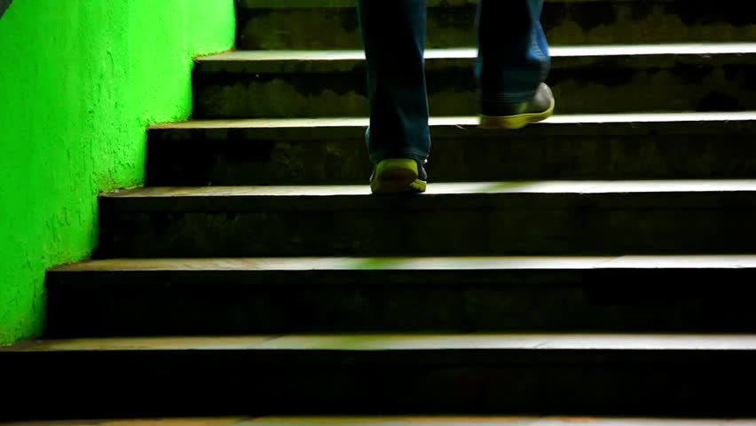 Young male on dark green staircase. Man in jeans and sneakers walking up the stars. Source: Canon 7D, graded. Clip ID: ax1217c