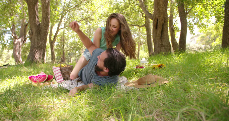 Playful young couple laughing and tickling each other while having a picnic in the park