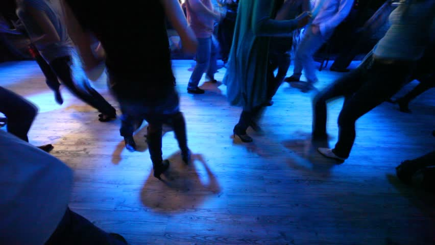 Legs of many dancing men and women in some nightclub with different colors blinking  - HD stock footage clip