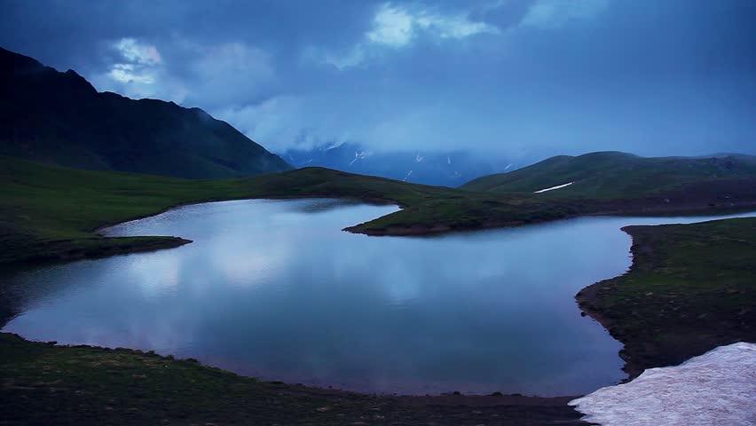 Majestic landscape with lake Koruldi and overcast sky at the foot of Ushba, Upper Svaneti, Mestia, Georgia, Europe. Caucasian ridge. Dramatic unusual scene. Beauty world. HD video (High Definition)