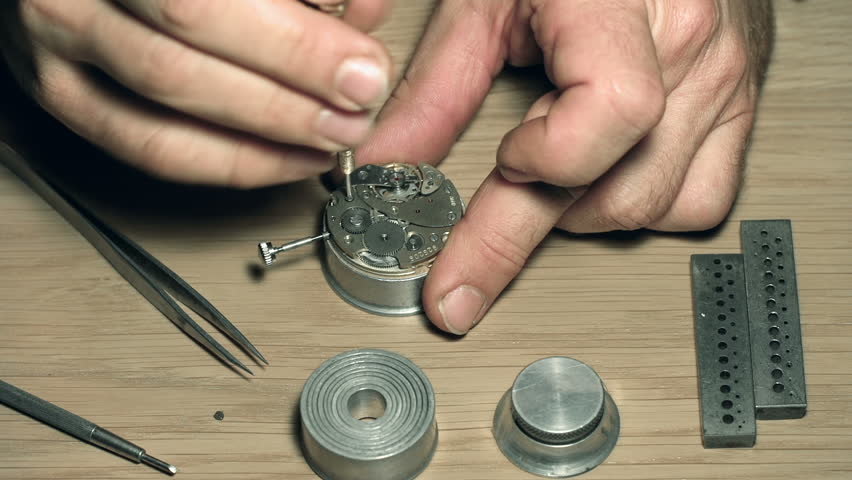 Close up of unrecognizable master disassembling watch with special tools