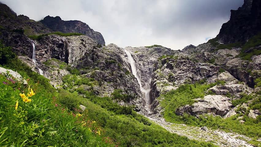 Powerful waterfall at the foot of Mt. Ushba. Upper Svaneti, Georgia, Europe. The main Caucasus ridge. Dramatic unusual scene. Beauty world. HD video (High Definition)