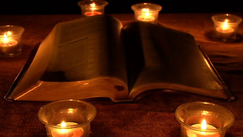 a book surrounded by candles
