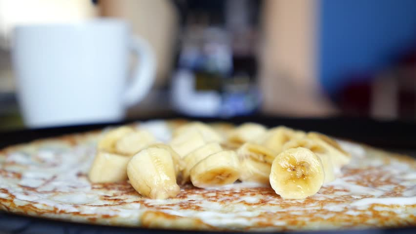Close-up Crepe Pancake with Bananas and Chocolate Syrup. Slow Motion. HD, 1920x1080.