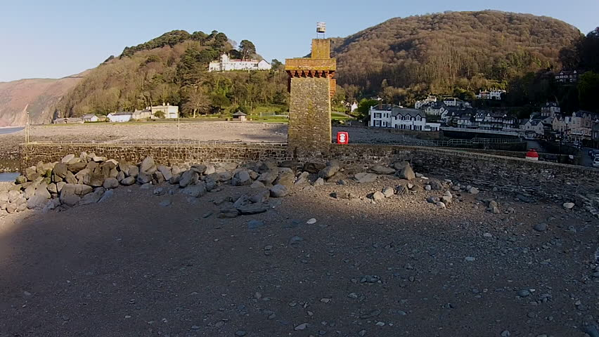 Aerial view from drone of the shoreline of Lynmouth with Rhenish Tower at sunset, Exmoor National Park, North Devon - HD stock footage clip