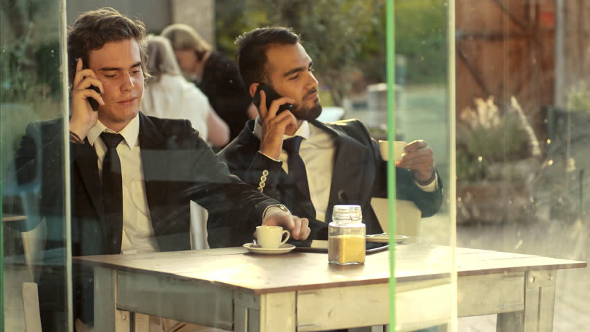 Smart phone men calling on mobile phone at coffee cafe. Handsome young multi-ethnic business men talking on smartphone, doing business and enjoying their coffee.