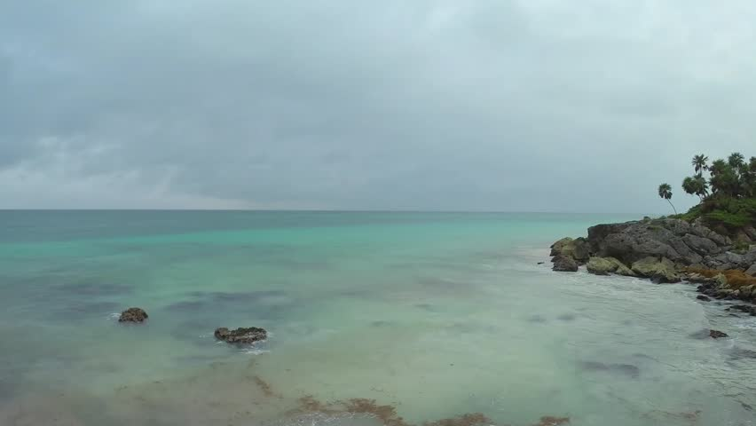 Gentle waves of turquoise green Caribbean Sea roll onto rocky rugged palm-fringed coastline near Tulum, Mexico under gray rainy sky with sounds of surf and birds - HD stock footage clip
