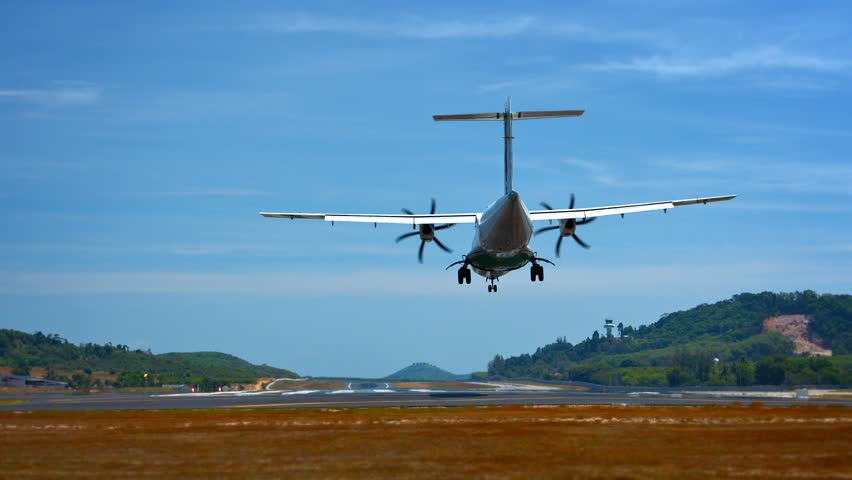 Video 1920x1080 - Small. turbo-prop commuter airplane lands at Phuket International Airport on a beautiful. sunny day. with a load of happy tourists. - HD stock footage clip