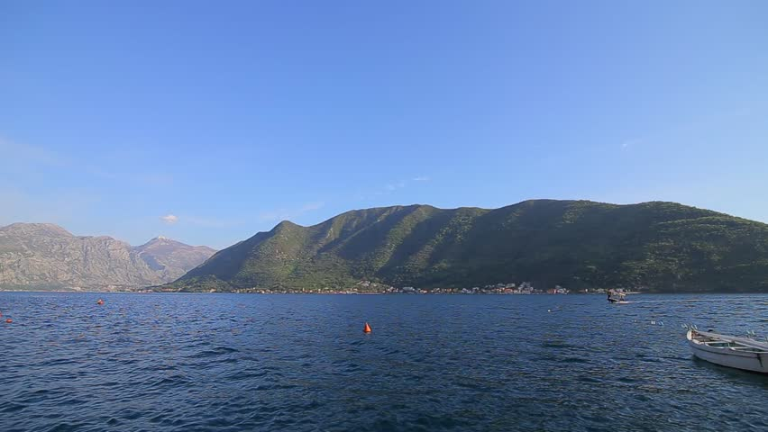 Boat in the Gulf. View of the mountains, sea and sky in the Bay of Kotor in Montenegro. Fishing boats and pleasure boats in Perast. Clear sky without clouds and small waves on the water