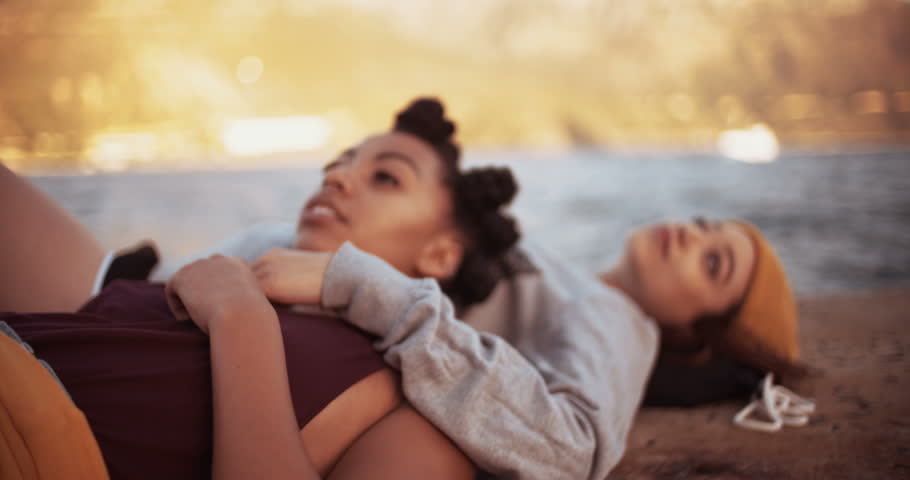 High angle view of two teen grunge girls lying together on a harbour wall alongside water, Panning in Slow Motion - 4K stock footage clip