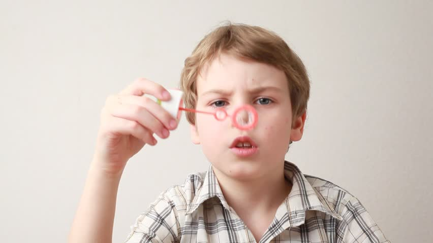 portrait of boy blowing soap bubbles on white background - HD stock video clip