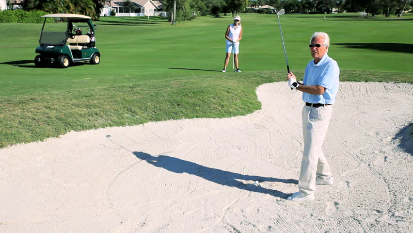 Retired gentleman driving out of a sand bunker on the golf course while his wife watches - HD stock footage clip