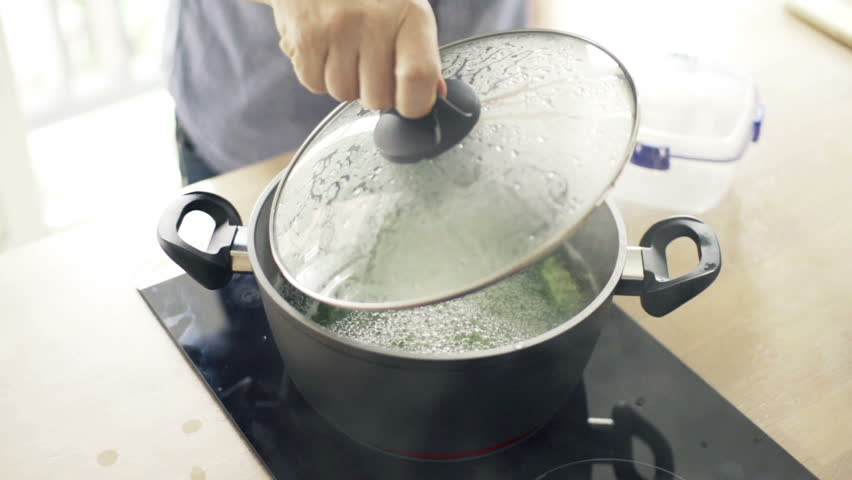 Boiling broccoli in pot in kitchen, slow motion shot at 240fps