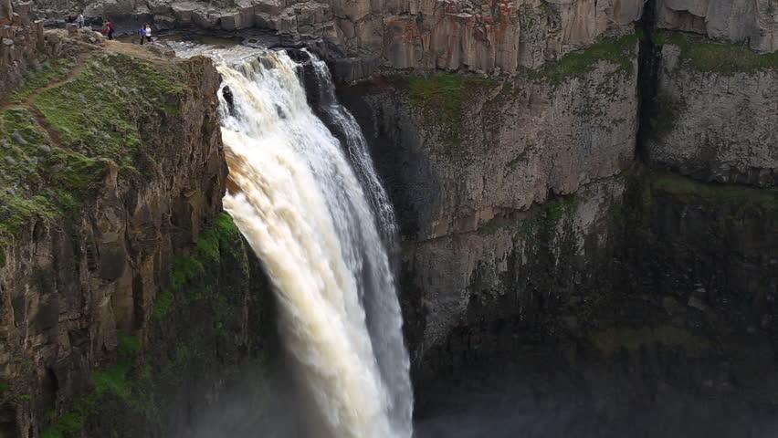 People hangout beside a waterfall
