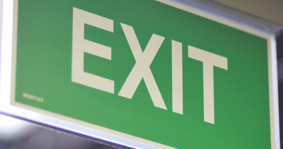 Footage of an exit sign-the shot is going into focus and goes again out of focus
