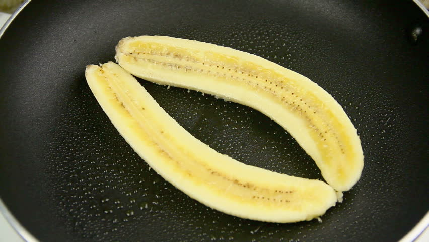 Slices of fresh banana being put into a pan with a spatula to fry.