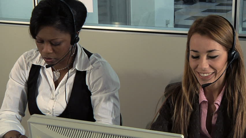 Multiethnic group of female customer service representatives talking on the phone and typing on computer keyboard. People working in call center. Shot on steadicam - HD stock footage clip