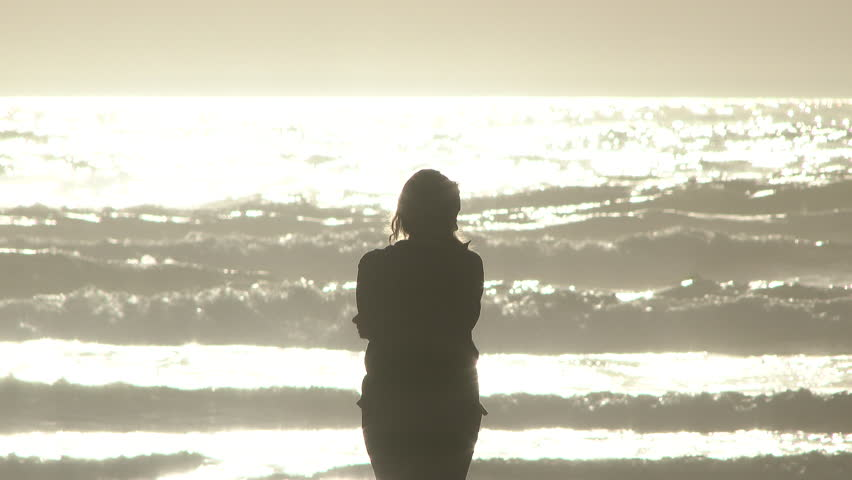 Woman stands at the Pacific Ocean on sunny day by herself.