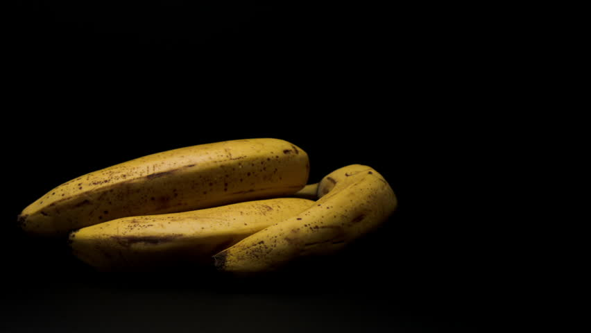 THREE BANANAS ON A DRAMATIC, MATTE BLACK, BACKGROUND ARE JOINED BY A FOURTH BANANA WITH A BITE TAKEN OUT. BANANA DROPS INTO A HIGH CONTRAST FRAME. - HD stock video clip